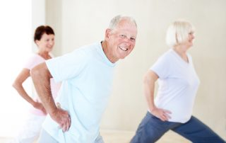 A group of elderly people stretching their legs together